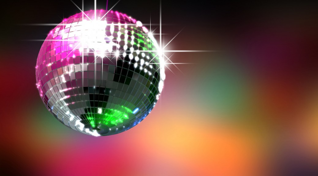 A colorful reflective disco ball with glinting highlights on a blurry colored background